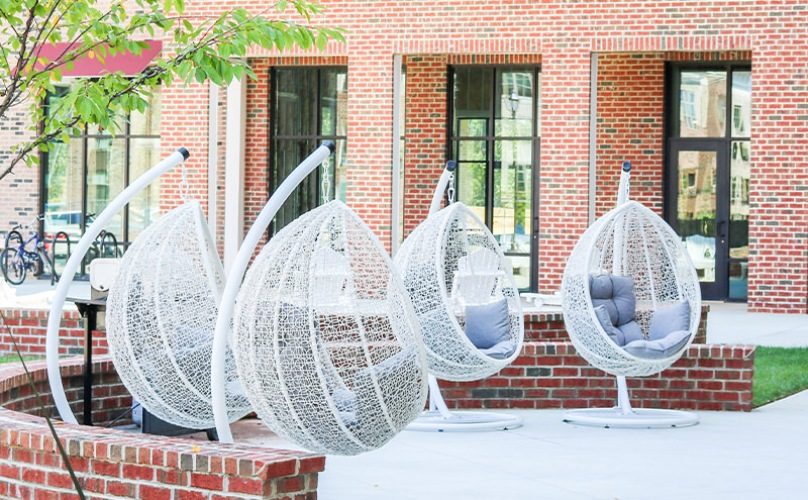 Modern hanging chairs are available in the open courtyard outside